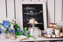 Summery flower arrangements and hand-writing sign on buffet table