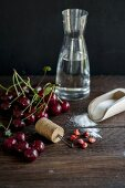 ingredients for cherry liqueur (alcohol, sour cherries, sugar) and a homemade cherry pitter