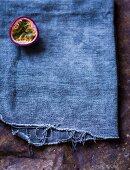 Half a passion fruit on a blue cloth