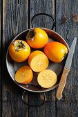 Persimmons, whole and halved, in a pan