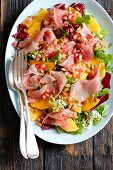 Persimmon salad with prosciutto, pumpkin seeds and pomegranate