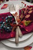 A place setting with antique cutlery decorated with autumnal leaves and berries