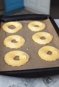 Piped choux pastry rings on a baking tray