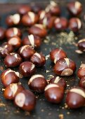 Roasted chestnuts on a baking tray