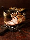 Carved rack of pork on a chopping board