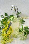 Elderflower syrup in a flip-top bottle, edlerflowers and a wreath of rape flowers