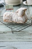 An Easter lamb cake dusted with icing sugar on a wire rack