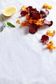 Deep-fried carrots and beetroot chips on a white surface