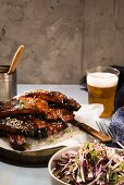 Glazed pork ribs served with coleslaw and a glass of ginger and peppermint beer