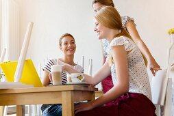 Drei junge Frauen bei einer Besprechung mit Laptop im Cafe
