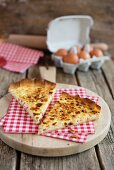 Two slices of quiche Lorraine with napkins on a wooden board