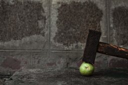 A green walnut with a hammer on a wooden table