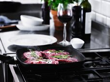Beef steaks with rosemary being fried in a pan