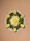 Potatoes, spinach and egg yolk arranged in a circle on a brown surface