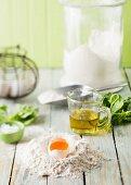 Ingredients for basic pasta recipe (flour, egg, olive oil, salt)