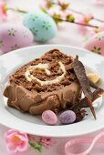 A slice of Easter chocolate log cake with chocolate cream and Easter eggs