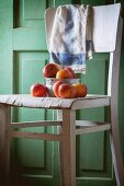 An aluminium bowl of red apples on an old white wooden chair against green wooden wall