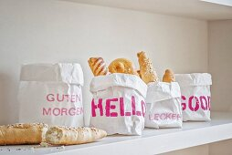 Paper bags printed with various stencilled mottos used as bread baskets