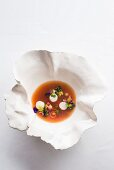 Vegetable and hibiscus tea broth with lobster medallions