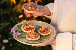 Savoury tartlets with tuna tartare, small slices of lime and peach