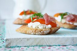Bruschetta with goats' cheese, almonds, tomato slices, cured ham and rocket