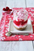 A layered dessrt with vanilla cream, biscuits, raspberries, pink meringues and lime zest