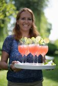 Cheerful woman serving tray of drinks in garden