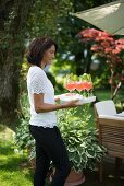Woman serving refreshing trays on tray in garden