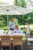 Three friends enjoying refreshing drinks around table in garden