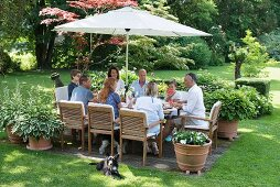 Guests around set table with integrated parasol in garden