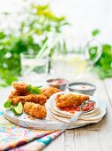 Mini crispy chicken fajitas and tortilla wraps with limes and tomato relish on a garden table