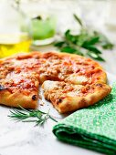 A sliced pizza with rosemary