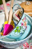 Vintage-style painted enamel colander and spatulas in bowl on garden table in sunshine