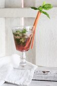 A rhubarb drink with ice cubes and mint in a glass, garnished with a rhubarb stick