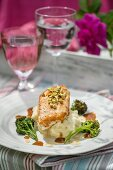 Chicken breast with broccoli and mashed potatoes on a table outside