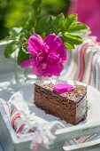 A slice of chocolate cake with cherry liqueur on a table outside