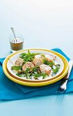Smoked salmon rolls filled with cream cheese on a bed of rocket with capers