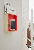 Holzkasten mit orangefarbener Innenwand als Ladestation für Handy
