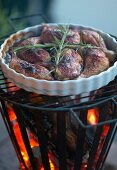 Grilled chicken legs and sprigs of rosemary in white flan dish on top of fire basket with barbecue grille