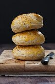 A stack of bagels on a wooden chopping board