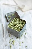 Dried organic peas in a small tin on an old linen cloth
