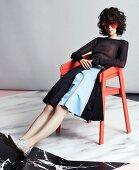 Junge Frau in Faltenrock und transparentem Pulli sitzt auf Stuhl