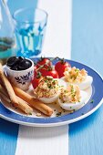 Devilled eggs filled with salmon trout served with olives, breadsticks and tomatoes