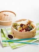Pancake rolls with Peking duck and spring onions in a bamboo steamer
