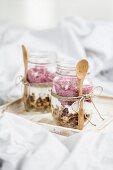 Muesli with yoghurt and raspberries in jars