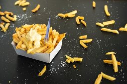 Chips in a paper dish with a chilli and honey mayonnaise