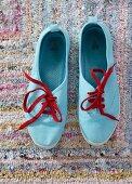 Hellblau gefärbte Sneakers mit roten Schnürsenkeln