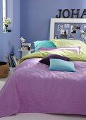 Gefärbte Kissenhüllen in verschiedenen Farben auf Bett mit violettem Plaid