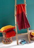 Handtuch in verschiedenen Rottönen gefärbt, auf Holzleiter gehängt