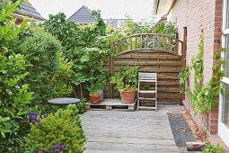 Holzterrasse mit Grünpflanzen und Sichtschutzzaun aus Holz